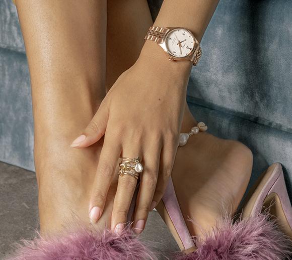 dolna część ciała kobiety z zegarkiem Waterbury z różowego złota na ręku i inną biżuterią